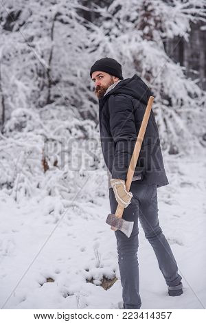 Bearded man with axe in snowy forest. Man lumberjack with ax. Camping, traveling and winter rest. skincare and beard care in winter, beard warm in winter. Temperature, freezing, cold snap, snowfall.