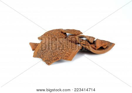 Pile of broken brown ceramic shards isolated on white background