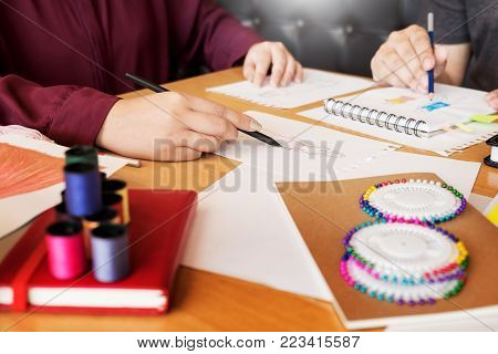young women working as fashion designer drawing sketches for clothes in atelier paper at workplace studio