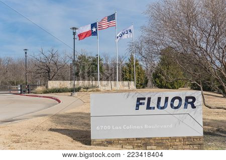 IRVING, TX, USA-JAN 14, 2018:Main entrance headquarters of Fluor Corporation. Multinational engineering, construction firm in the Fortune 500 rankings. US, Texas, company flags flying, cloud blue sky