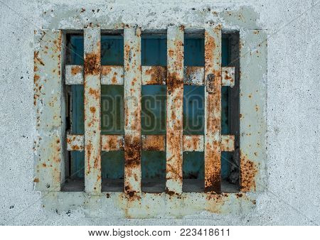 The concrete wall is a window, closed the old rusty grate