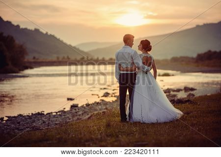 Sensitive wedding back shot. Peaceful beautiful newlyweds are hugging and looki at each other on the river bank during the sunset