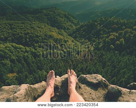 Naked male legs on peak make step. Sandstone rock above valley with tired hikers legs without shoes.  Outdoor activities in hot summer muggy weather.