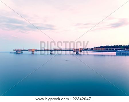 Romantic morning in harbor. Tourists resort, pier above silent blue water. Sunny pink blue sky. The smooth water level because long exposure