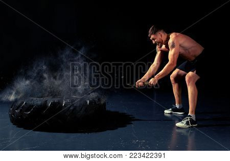 Man hitting wheel tire with hammer sledge. Crossfit training