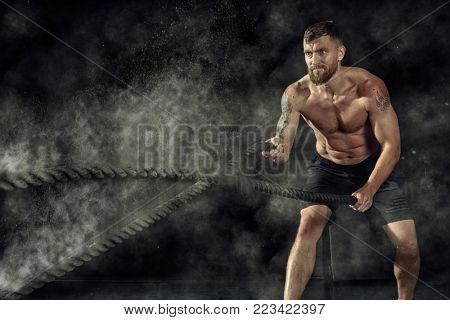 Crossfit training. Man working out with battle ropes at gym