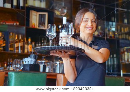 A brunette barmaid girl carries a bottle of wine with wine glasses on a tray to the client of the hotel bar. The concept of service.