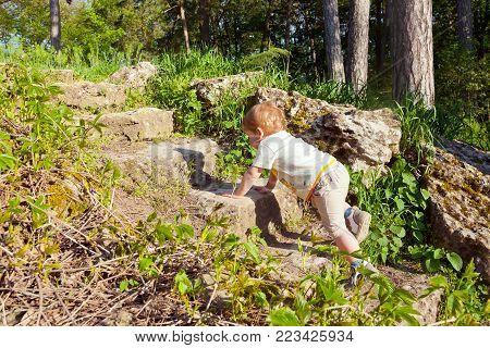 Little boy stubbornly climbs the stone steps.