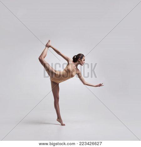 young beautiful dancer in beige swimsuit posing on light grey studio background