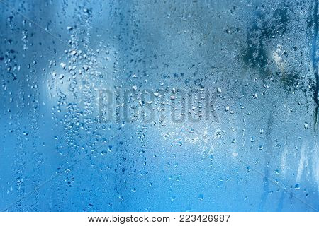 Condensing on the windows strong, high humidity in the room, cold tone. Natural water drop background