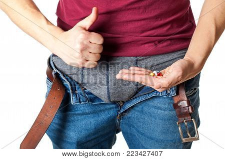 Close up picture of man's crotch with unzipped jeans holding potency pills