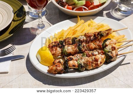 Chicken souvlaki cooked on grill served with french fries, half of lemon in greek tavern. Horizontal. Close-up.