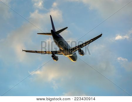 Passenger airplane in the clouds at sunset