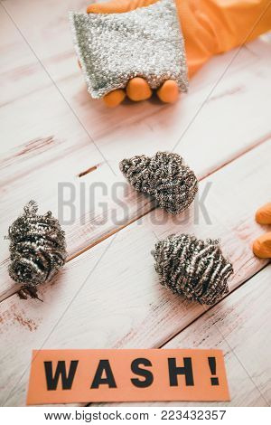 Keep your house clean. Steel scrub sponges on white wooden background, a hand in an orange latex glove holding a sponge and Wash inscription
