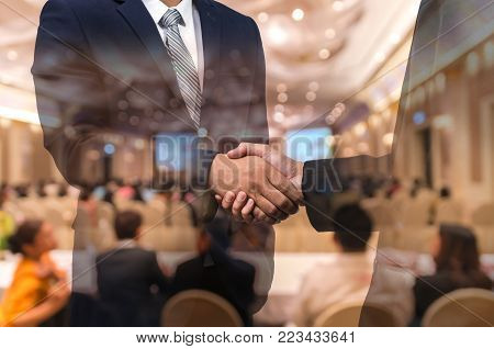 Double exposure of businessman handshake over the Abstract blurred photo of conference hall or seminar room with attendee background, business agreement concept, 3D illustration