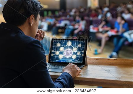 Businessman sitting and using computer laptop showing the Social media symbol over the Meeting Blurred background at bright conference hall, Business meeting concept