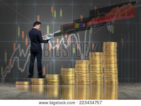 Asian Businessman standing over the stack of gold coins and using the tablet present the trading graph of Stock exchange market on trade graph background, Business trading and education concept, 3D illustration