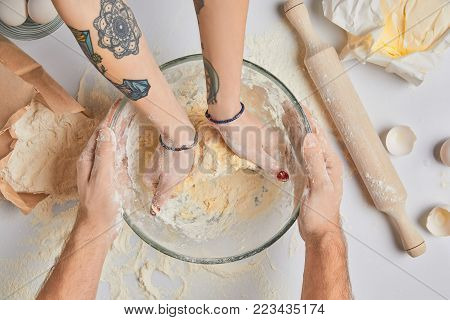 cropped image of chefs kneading dough in bowl