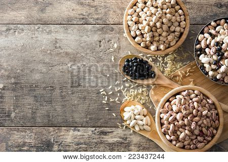 Uncooked assorted legumes in wooden bowl .Top view copy space on wooden table
