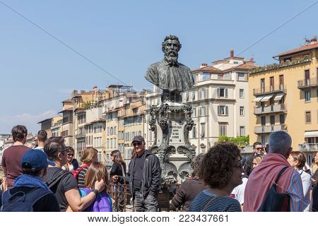 Florence, Italy - April 09, 2017: Tourists are photographed next to the bust of Benvenuto Cellini on the bridge Ponte Vecchio