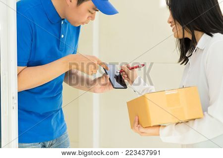 Delivery man pointing on smartphone and woman receiving package and signing on digital mobile phone.