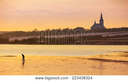 undefined person skating on the frozen lake in evening. beautiful winter countryside scenery. village and church in a far distance