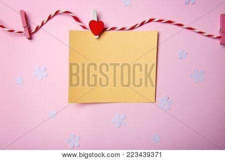 Empty card, string and pegs on color background