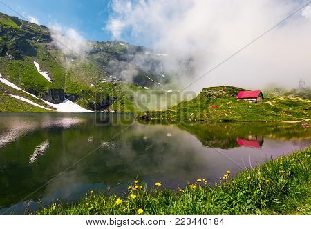 woodshed on the grassy shore of Balea lake. beautiful landscape in Fagaras mountains with rising cloud on summer day