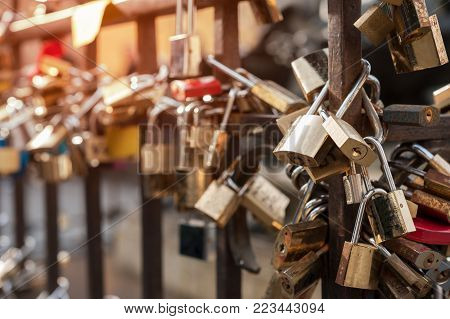 Many love padlocks locked on rusty iron gate at Old Bridge, in Florence.