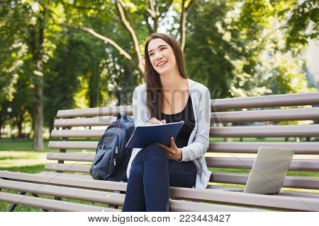 Smiling student girl sitting on bench in park, working with laptop and taking notes, preparing for exams outdoors, having rest in university campus, copy space