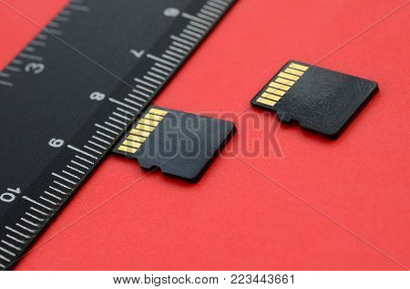 Two small micro SD memory cards lie on a red background next to a black ruler. A small and compact data and information store
