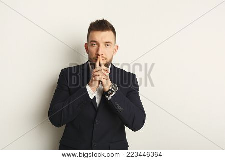 Handsome young caucasian businessman posing in studio and holding fingers on mouth on white isolated background. Confident serious man in formal clothes, copy space