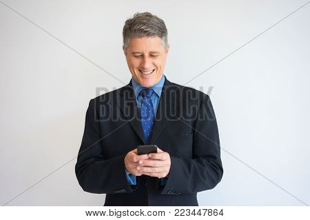 Portrait of happy mature North American businessman wearing formal suit holding mobile phone and texting message or networking. Mobile communication and mobile application concept