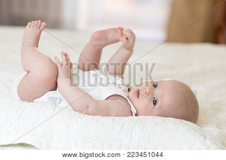 Funny baby infant girl playing with feet