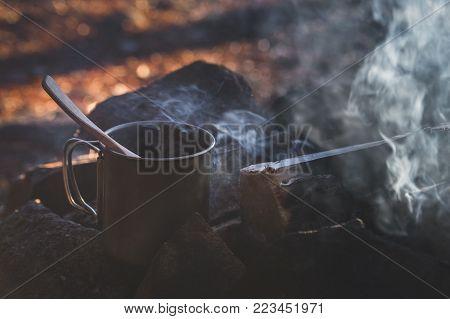 Smoking fire and steel mug full of hot coffee