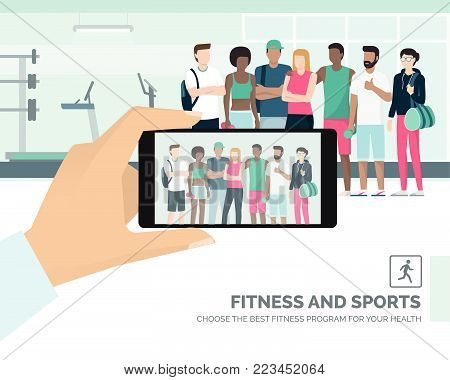 Young multi-ethnic sportspeople posing together at the gym, a man is taking a picture and sharing it online, subjective point of view