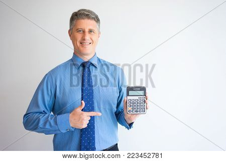Portrait of mature Caucasian accountant wearing shirt and tie showing calculator, looking on camera and smiling. Banking, finance, economy concept