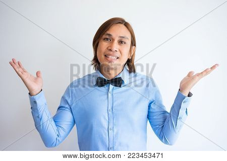 Portrait of smiling young Asian businessman wearing shirt and bowtie looking at camera and shrugging shoulders. Confusion and ignorance concept