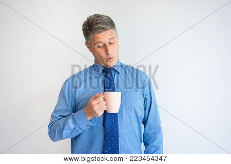 Portrait of surprised happy mature Caucasian businessman wearing shirt and tie holding coffee cup and looking into it. Coffee break concept