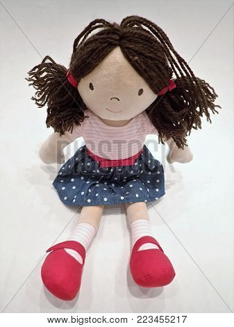 Child's rag doll toy with pigtails, blue dress and red shoes