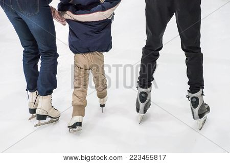 Happy family ice skating at rink. Winter activities
