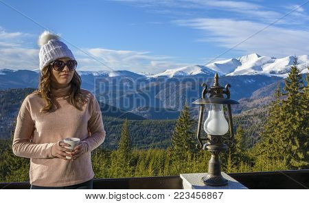 Young tourist lady, relax on the restaurant terrace, with a cup of tea in hand on December 26, 2017 in Ranca resort, Romania.