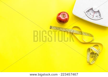 Proper nutrition for lose weight. Scale, measuring tape, apple on bright yellow background top view space for text.