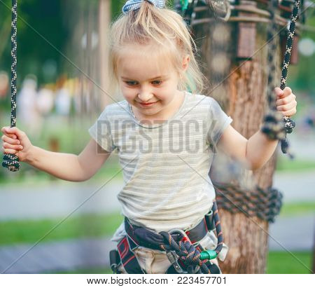 Cute girl enjoying activity in a climbing adventure park. Girl goes on hinged trail.