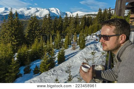Young tourist man, drinking a hot mulled wine on the restaurant terrace, relaxing and looking to the beautiful mountain view on December 26, 2017 in Ranca resort, Romania.