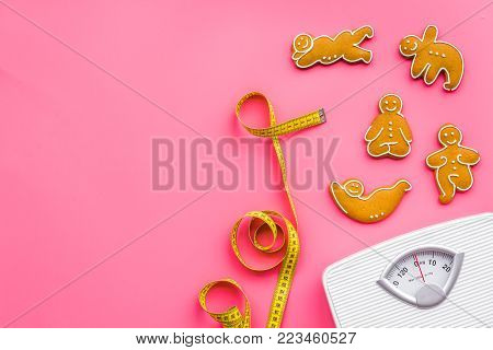 Ways for lose weight. Sport. Cookies in shape of yoga asans near scale and measuring tape on pink background top view.