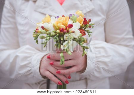 Woman holding flowers at the park. Close up. Toned image.