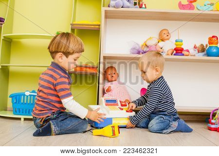 Two little boys are playing in the role of cashier and buyer in the kindergarten