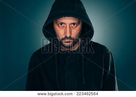 Serious portrait of adult man with hoodie looking at camera