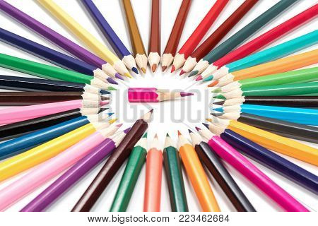 Brown pencil indicates a short pink pencil in the middle of a circle of pencils isolated on a white background